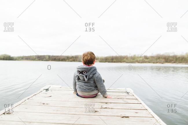 Boy sitting on dock looking at lake