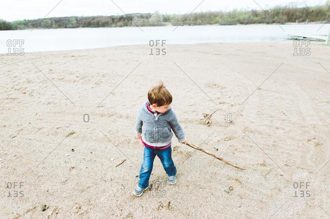 Boy dragging stick on lake shore
