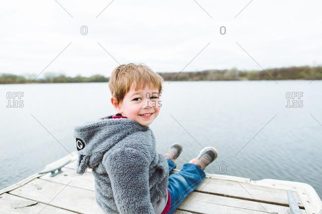 Smiling boy on a lake's dock
