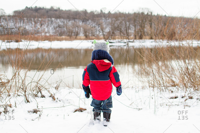 Boy at edge of a winter pond