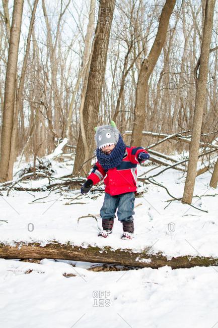 Boy on log in winter setting