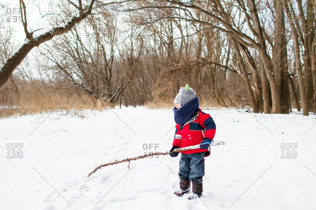 Boy holding stick in rural winter setting