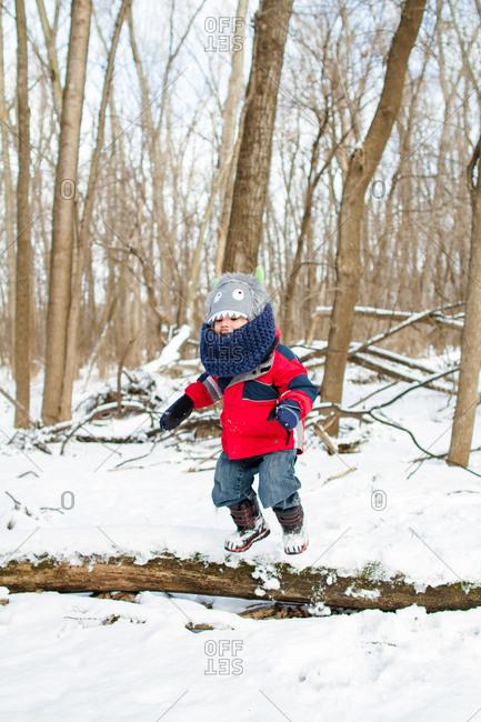 Boy balancing on log in winter setting