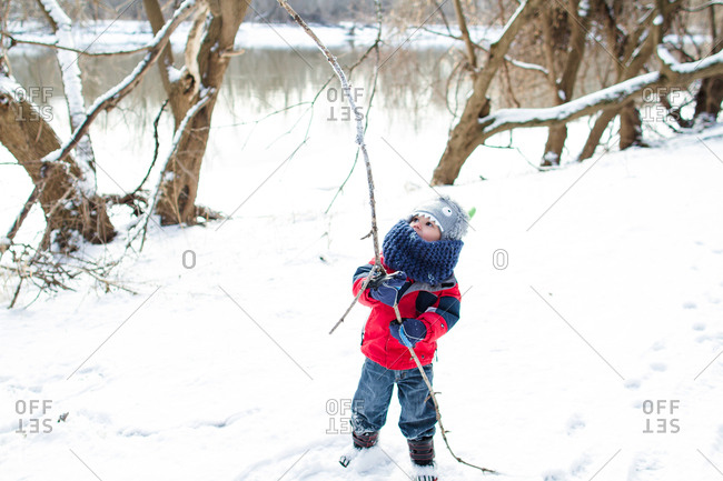 Boy with stick in rural winter setting