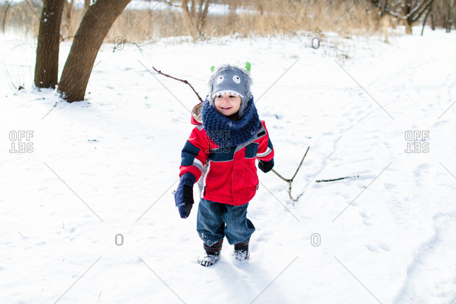 Boy dragging stick in winter setting