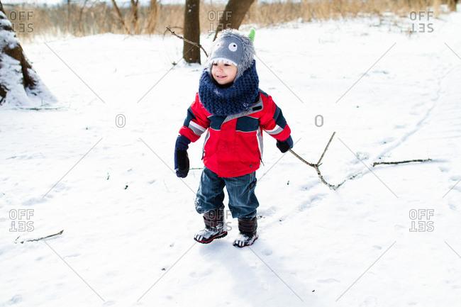 Boy dragging stick in winter field