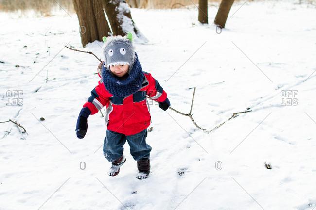 Boy dragging a stick in winter setting
