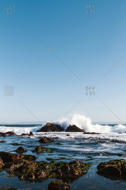 Waves splashing over boulders by shore