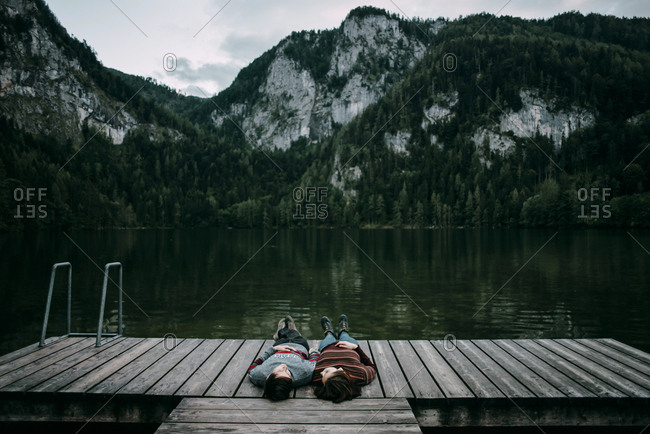 Caucasian couple laying on dock near scenic view of mountain