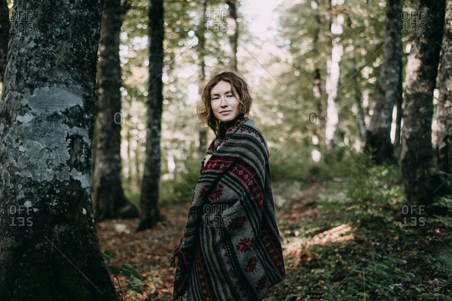 Caucasian woman wearing shawl in forest