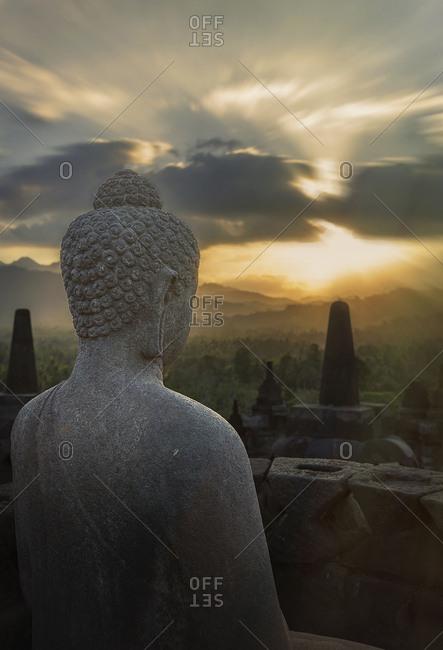 Statue of Buddha at sunset, Borobudur, Java, Indonesia