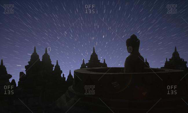 Silhouette of statue of Buddha at sunset, Borobudur, Java, Indonesia