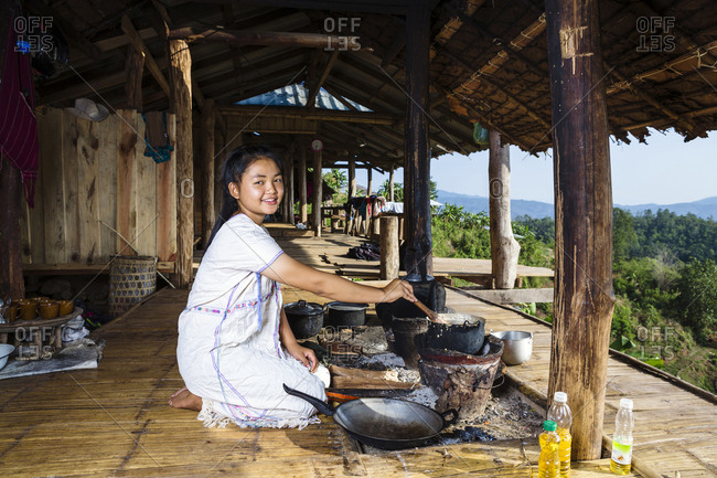 Smiling Asian woman cooking on patio outdoors