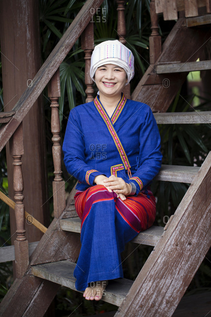 Asian woman wearing traditional clothing sitting on staircase