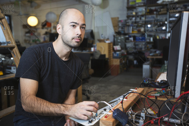 Mixed Race man working with electronics in workshop