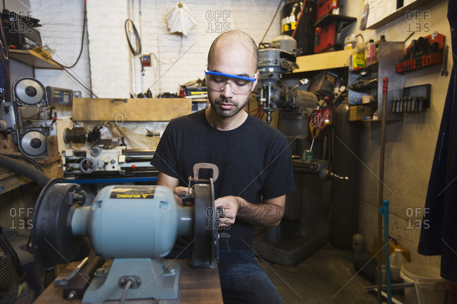 Mixed Race man using machinery in workshop