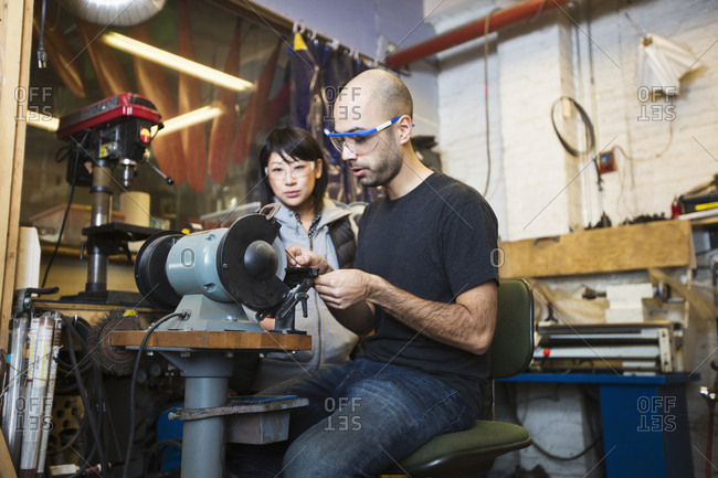 Man and woman using machinery in workshop