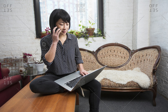 Asian woman talking on cell phone and using laptop