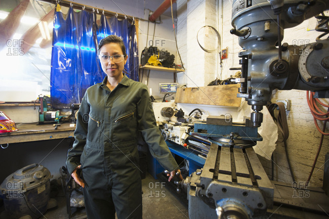 Mixed Race woman posing near machinery in workshop