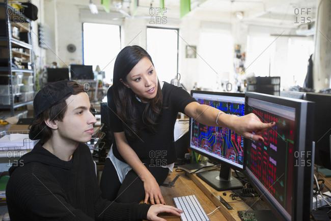 Man and woman examining circuits on computer monitors
