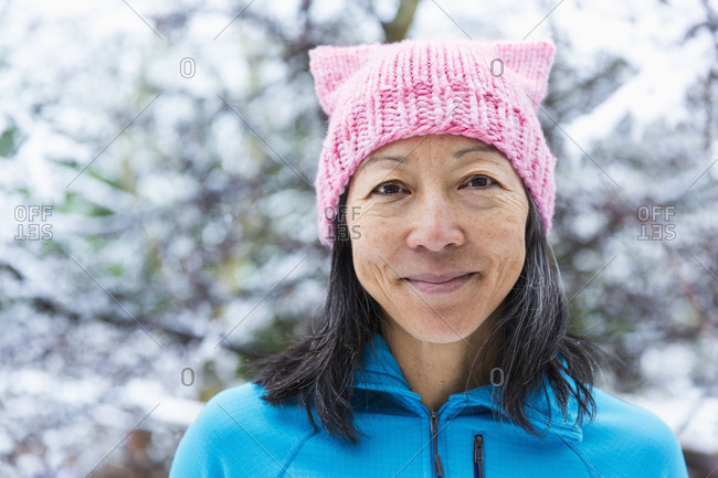 Smiling Japanese woman wearing pink hat with ears