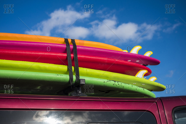 Multicolor surfboards strapped to roof of car