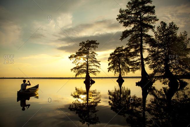 Reflection of Caucasian boy in canoe near trees in river