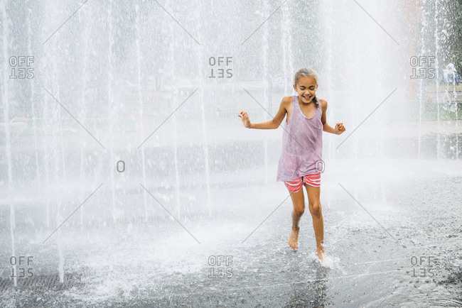 Smiling Mixed Race girl running fountain