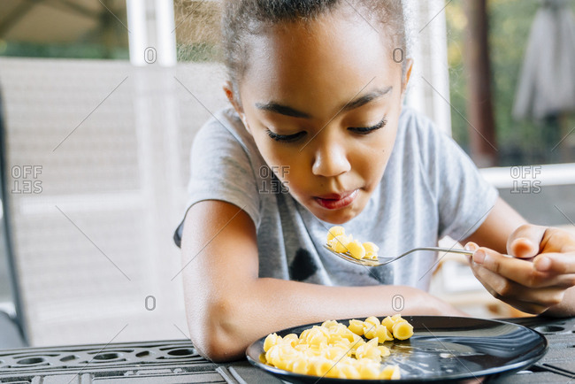 Mixed Race girl eating food with fork