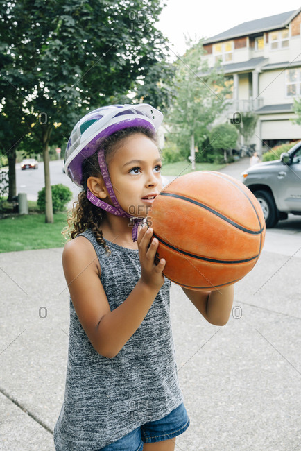 Mixed Race girl wearing helmet playing basketball in driveway