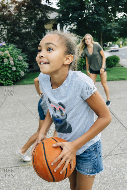 Mother and daughters playing basketball in driveway