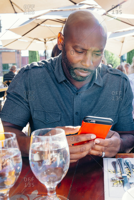 Black man sitting at restaurant table texting on cell phone