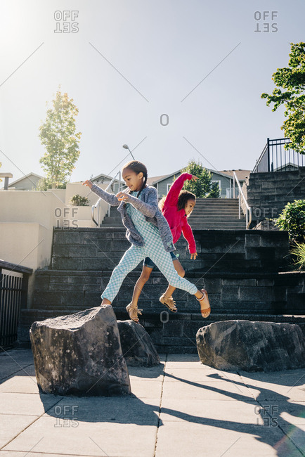 Mixed Race sisters jumping on rocks