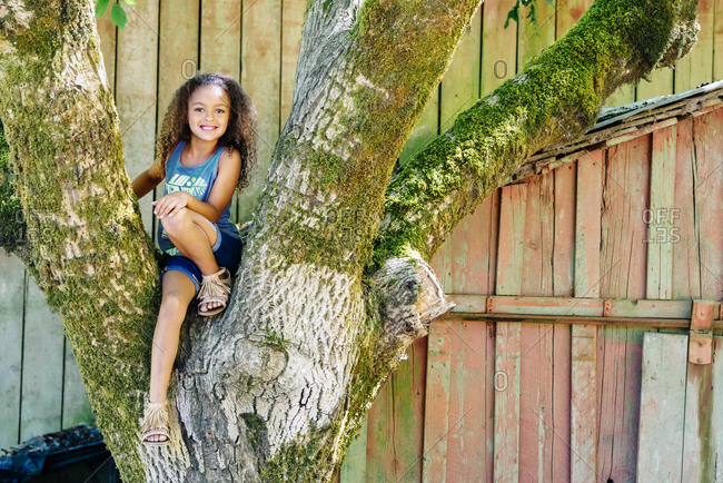 Mixed Race girl sitting in tree