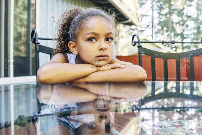 Pensive Mixed Race girl leaning on glass table
