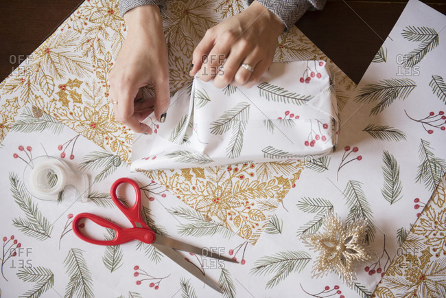Hands of Caucasian woman wrapping Christmas gifts