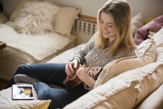 Smiling woman sitting on sofa playing ukulele