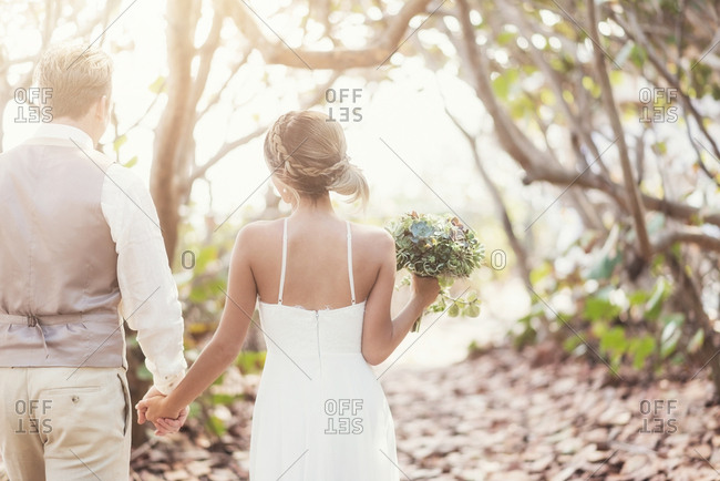 Caucasian bride and groom holding hands outdoors