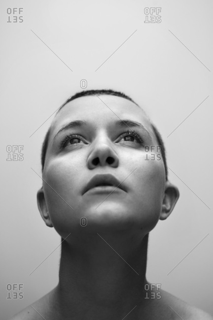 Caucasian woman with shaved-head looking up