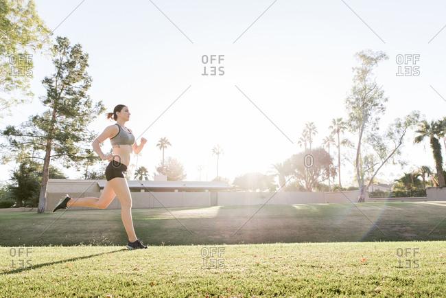 Caucasian woman running on grass in park