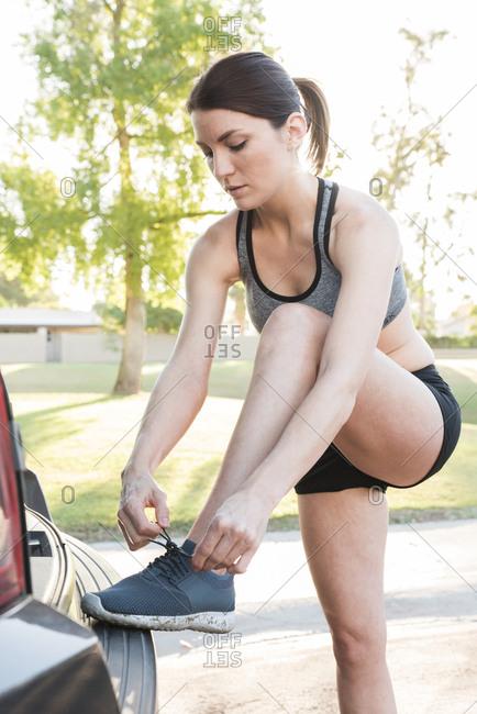 Caucasian woman leaning on car bumper tying shoelace