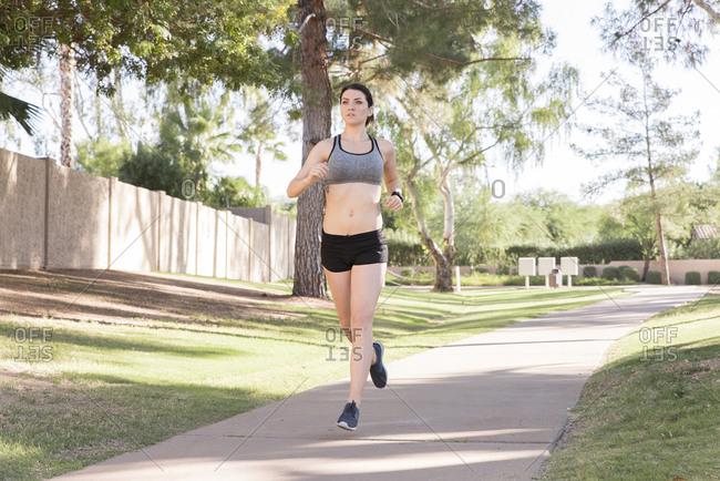 Caucasian woman running on path in park