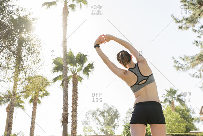 Caucasian woman stretching arms under palm trees