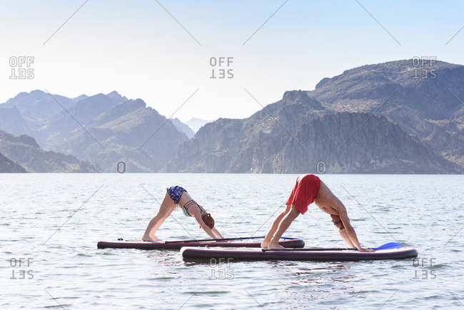 Couple stretching on paddleboards in river