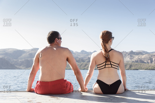 Couple sitting on dock at river