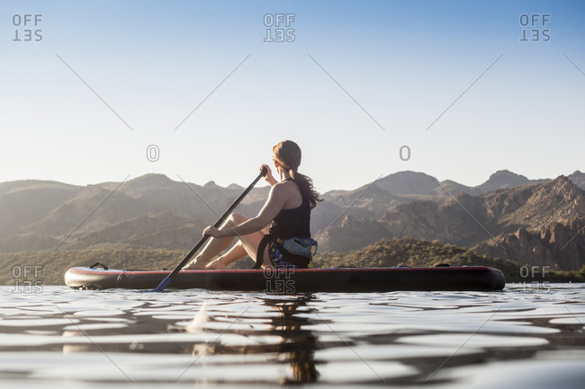 Caucasian woman sitting on paddleboard in river