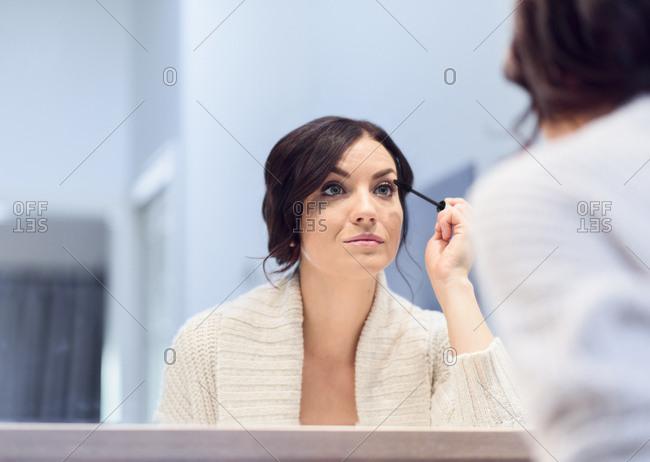Caucasian woman applying mascara in mirror