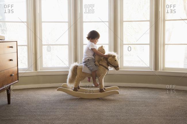 Mixed Race boy sitting on rocking horse near window