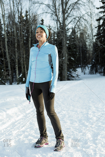 Black runner listening to cell phone with ear buds in winter