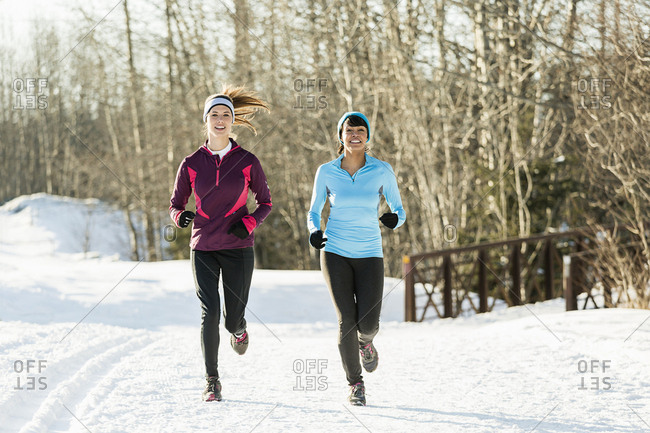 Women running on snow in winter